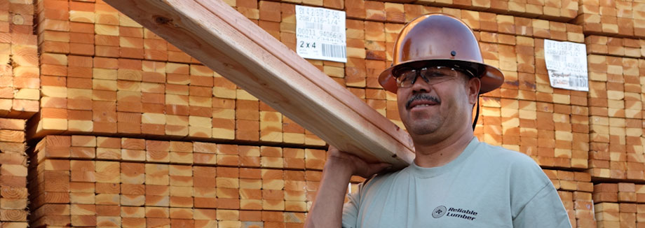 Image of reliable employee carrying lumber